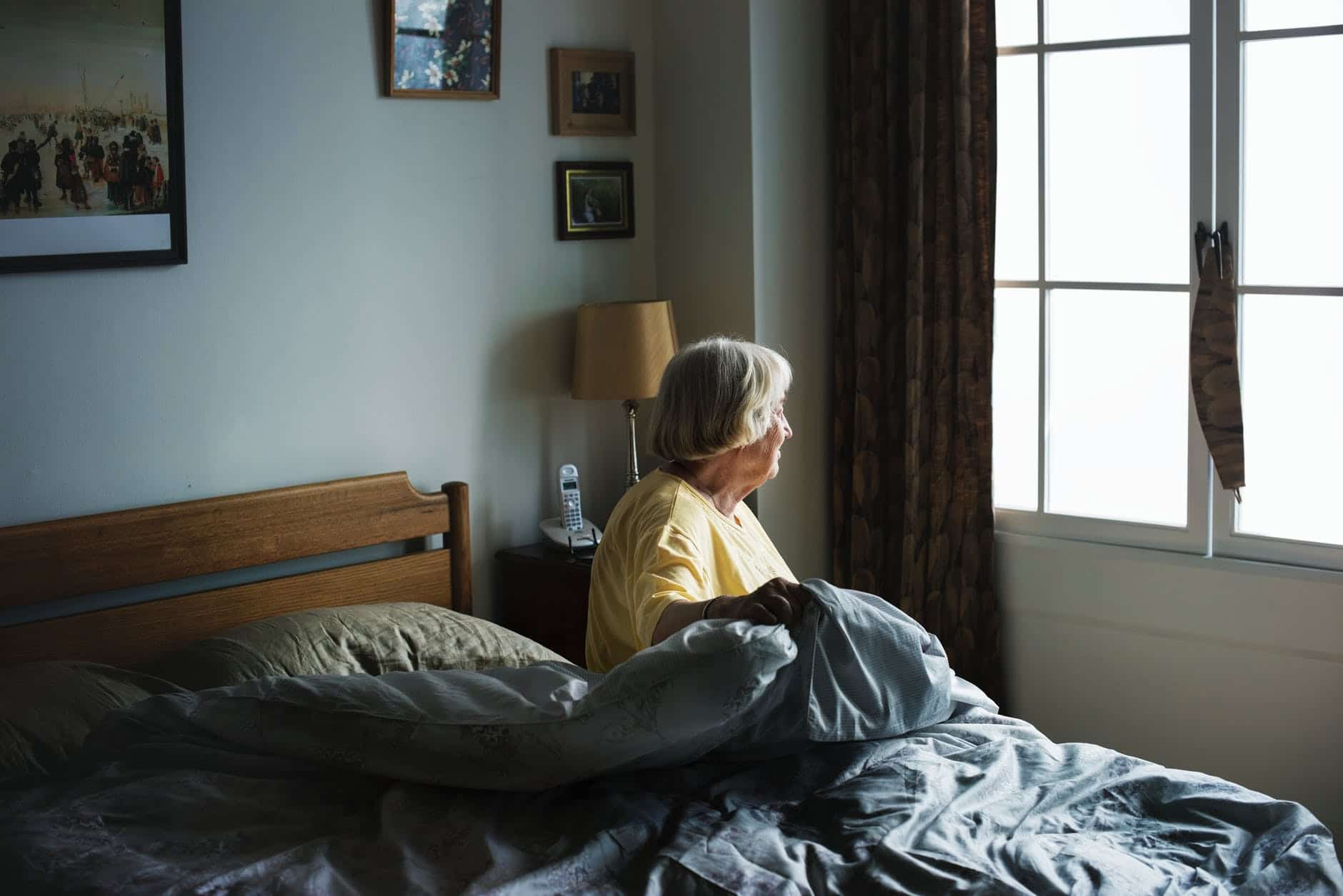 An elderly woman sits in bed, looking out a window.