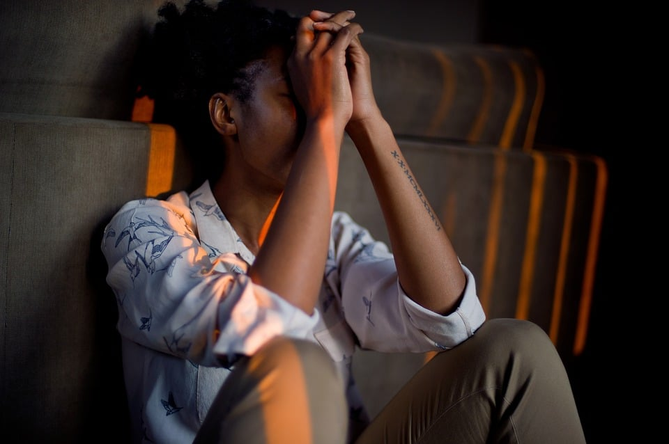 A woman sits in darkness, her head in her hands.